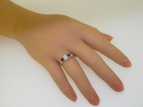 opal and cab garnet trilogy ring on hand