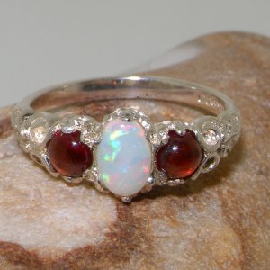 victorian inspired ornate opal and garnet trilogy ring on rock