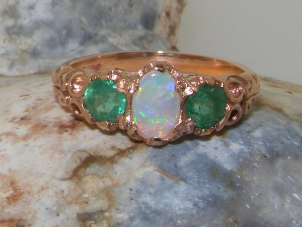 ornate rose gold opal and emerald trilogy ring on rock