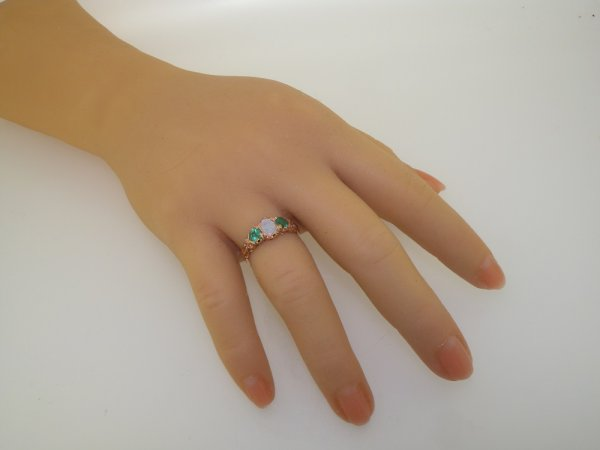 opal and emerald rose gold ring on hand