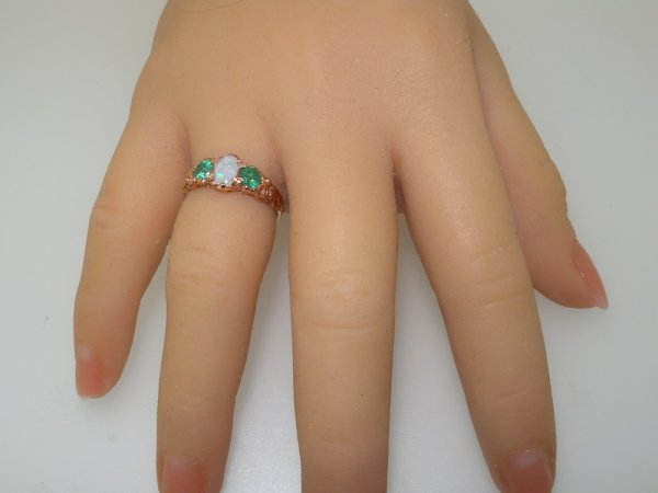 ornate opal and emerald rose gold ring on hand