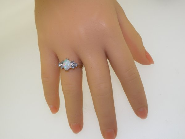 opal and aquamarine ring on hand