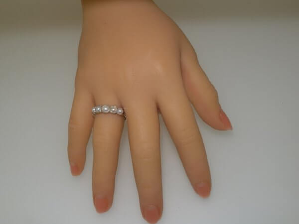 gold eternity ring set with pearls on hand